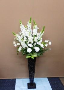 お誕生日のお祝いに清楚な白のスタンド花